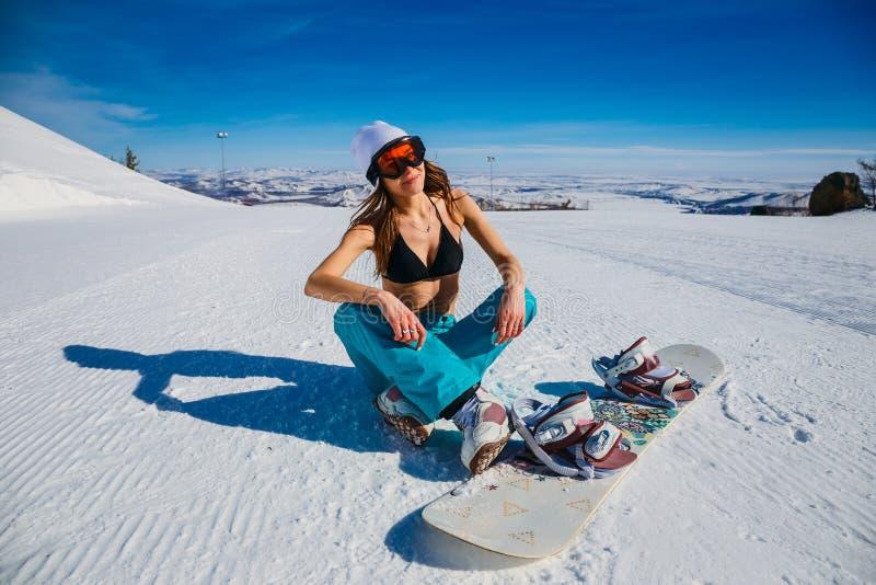 Snowboarder sexy della donna nella maschera arancio che si siede nella neve Donna in costume da bagno nell'inverno immagine stock libera da diritti