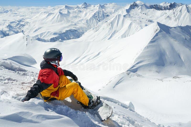 Snowboarder siedzi wysoko w górach na krawędzi skłonu zdjęcie royalty free