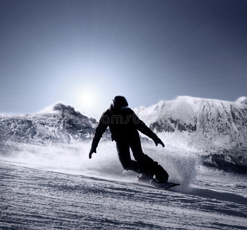 Snowboarder silhouette goes down by the high mountain ski slope royalty free stock image