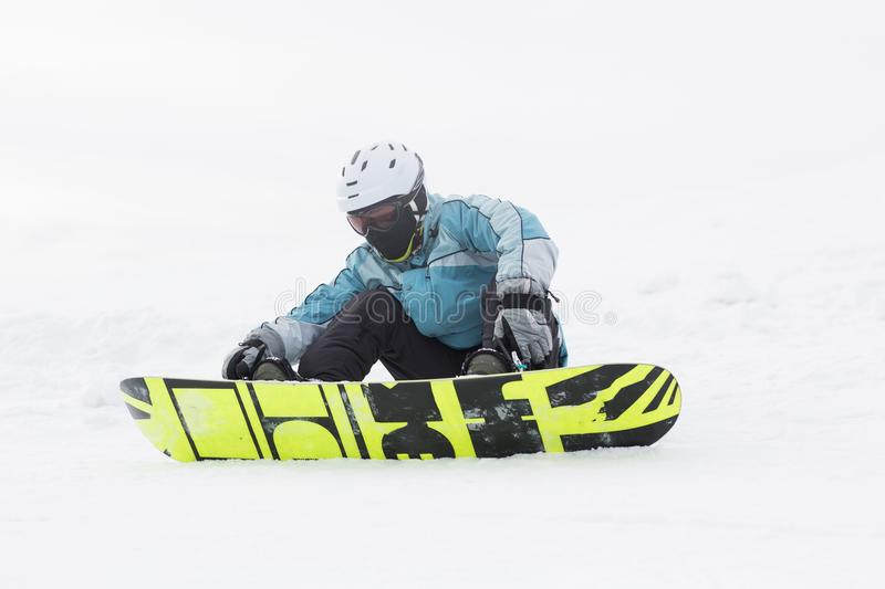 Snowboarder sitting on a hillside high mountain stock photography