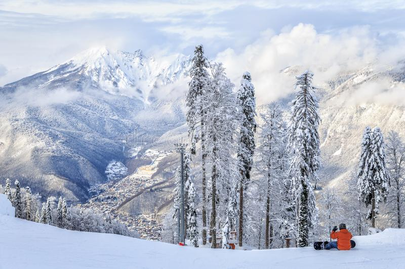 A snowboarder sitting on the snowy winter mountain slope of Sochi ski resort. Beautiful scenic landscape. Man snowboarder sits on snowy winter mountain slope in royalty free stock image