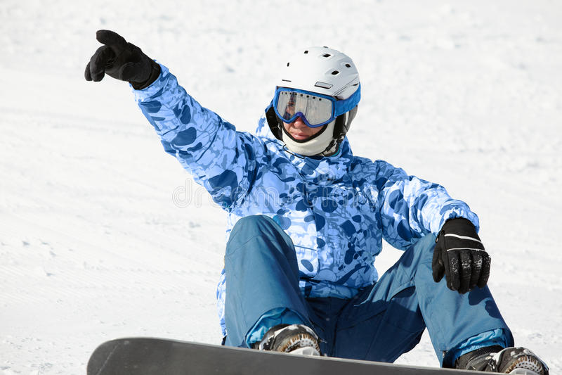 Snowboarder sitzt auf schneebedecktem Abhang stockbilder
