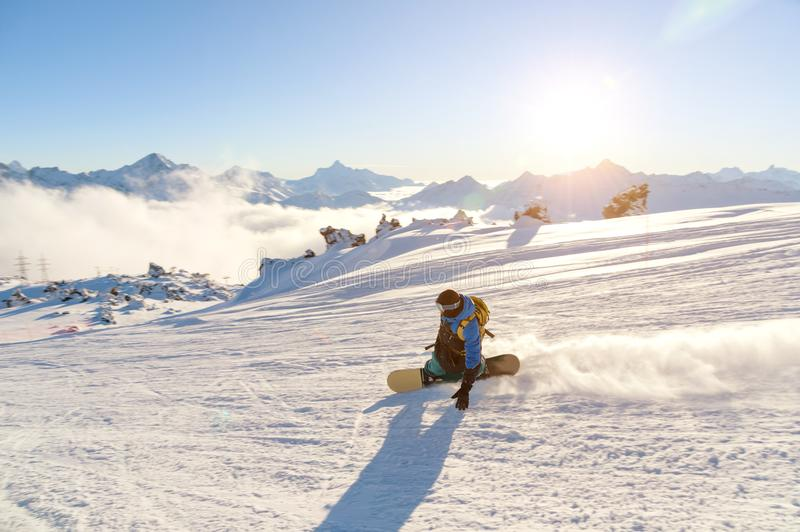 A snowboarder in a ski mask and a backpack is riding on a snow-covered slope leaving behind a snow powder against the stock photo