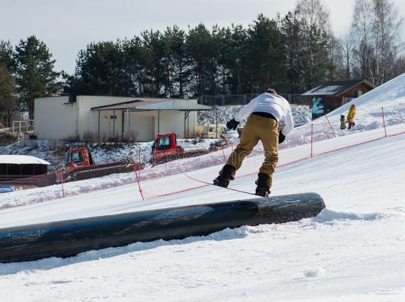 Snowboarder slides on rails royalty free stock photos