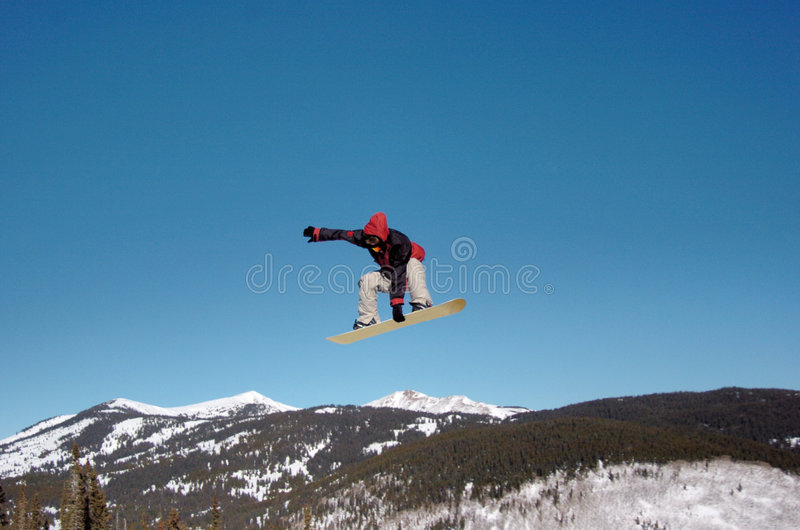 Snowboarder sobre as Montanhas Rochosas foto de stock
