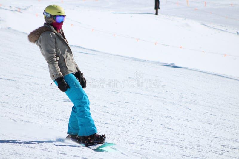 Snowboarder som går ner lutningen arkivbild