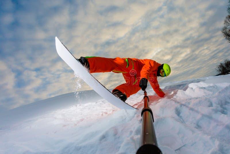 Snowboarder som gör ett trick och gör en selfie royaltyfri bild