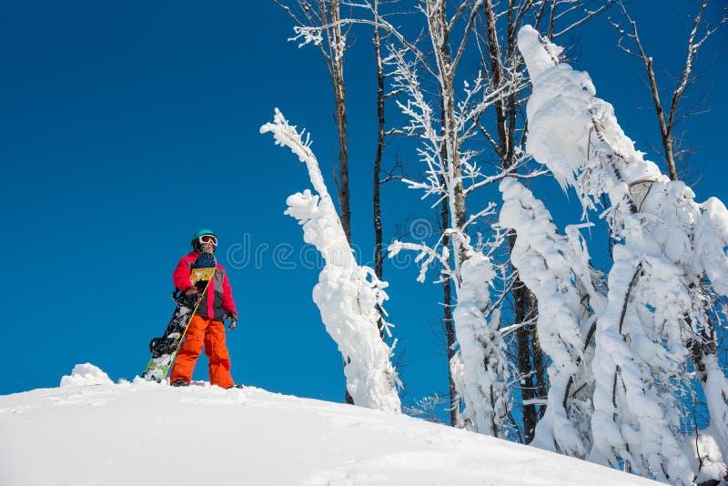 Snowboarder som undersöker snöig berg royaltyfria bilder
