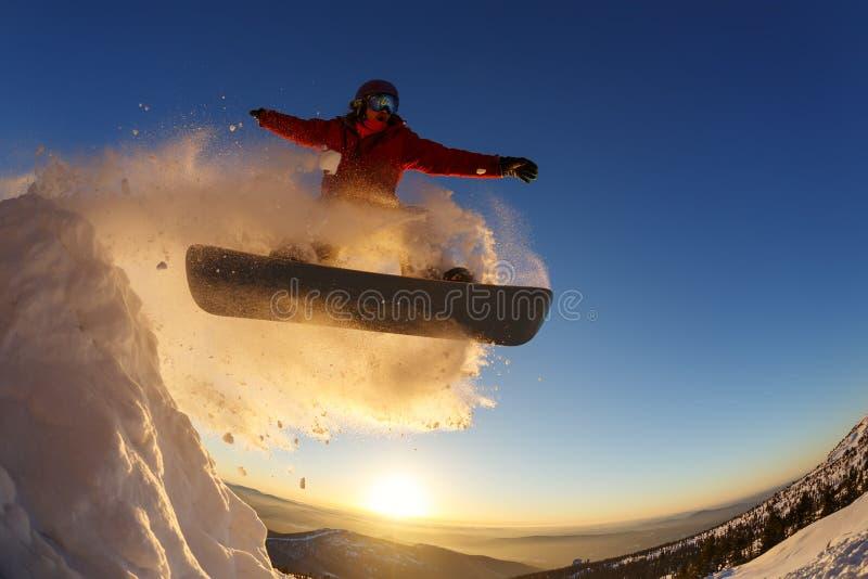 Snowboarder springt durch die Luft mit tiefblauem Himmel im Hintergrund lizenzfreie stockfotos