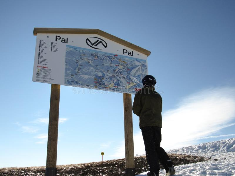 Snowboarder stand before map of pistes. Andorra,PAL -December, 2011 royalty free stock photography