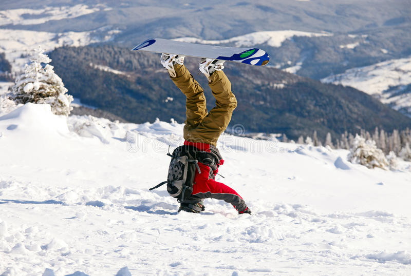 Snowboarder standing on his head in snow royalty free stock image