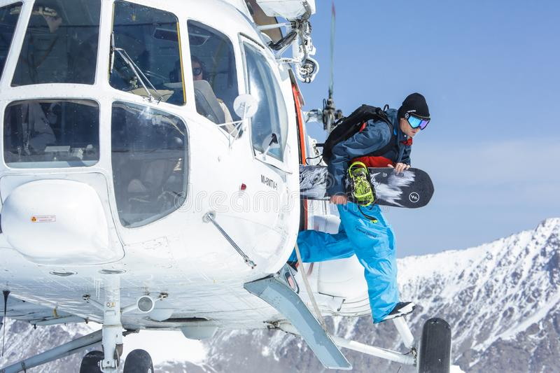 Snowboarder stepping out of helicopter stock photo