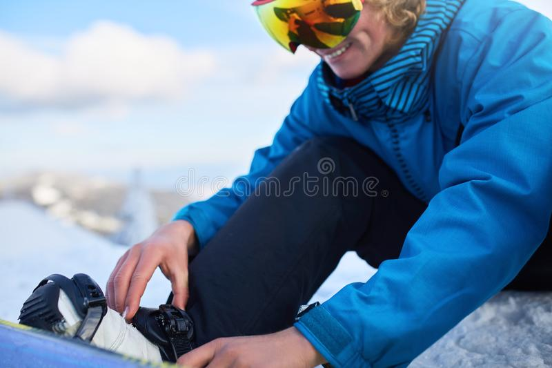 Snowboarder straps in his legs in snowboard boots in modern fast flow bindings with straps. Rider at ski resort prepares royalty free stock photography