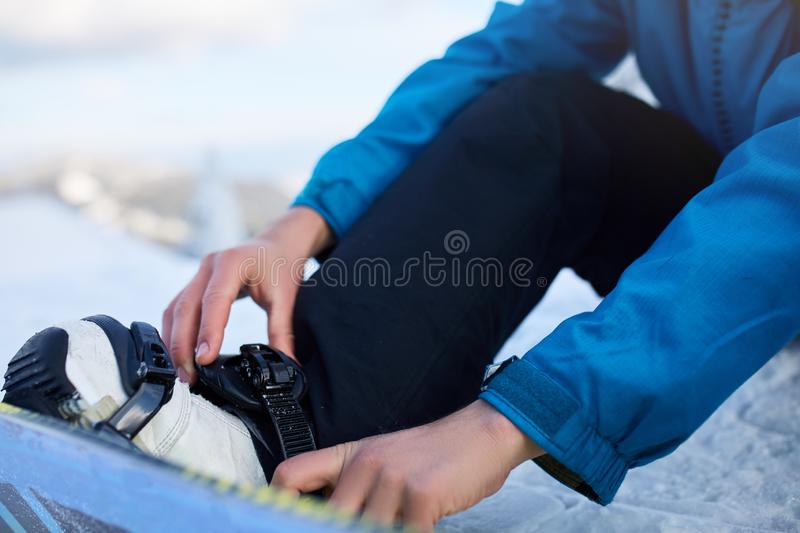 Snowboarder straps in his legs in snowboard boots in modern fast flow bindings with straps. Rider at ski resort prepares. For freeride session and fastens his royalty free stock image