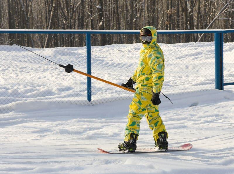 Snowboarder in un vestito giallo fotografie stock