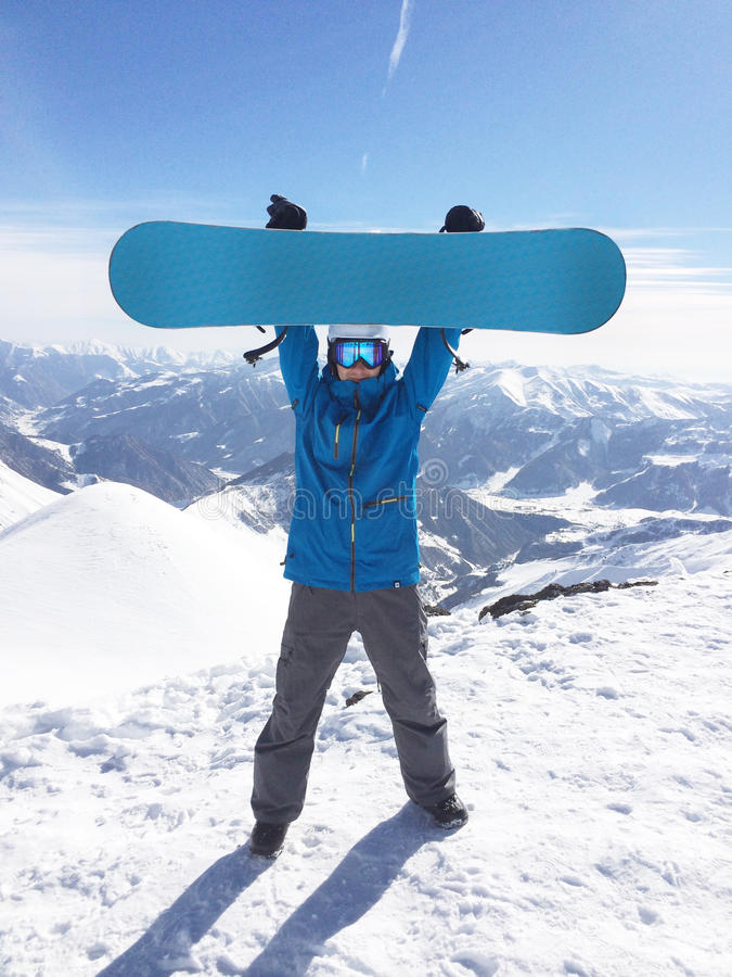 Snowboarder up hold snowboard on top of hill royalty free stock photo