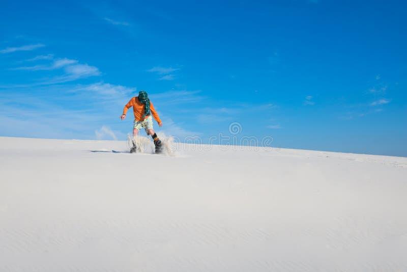 Snowboarder, vestindo uma aterrissagem do lenço após o salto em uma duna de areia imagem de stock