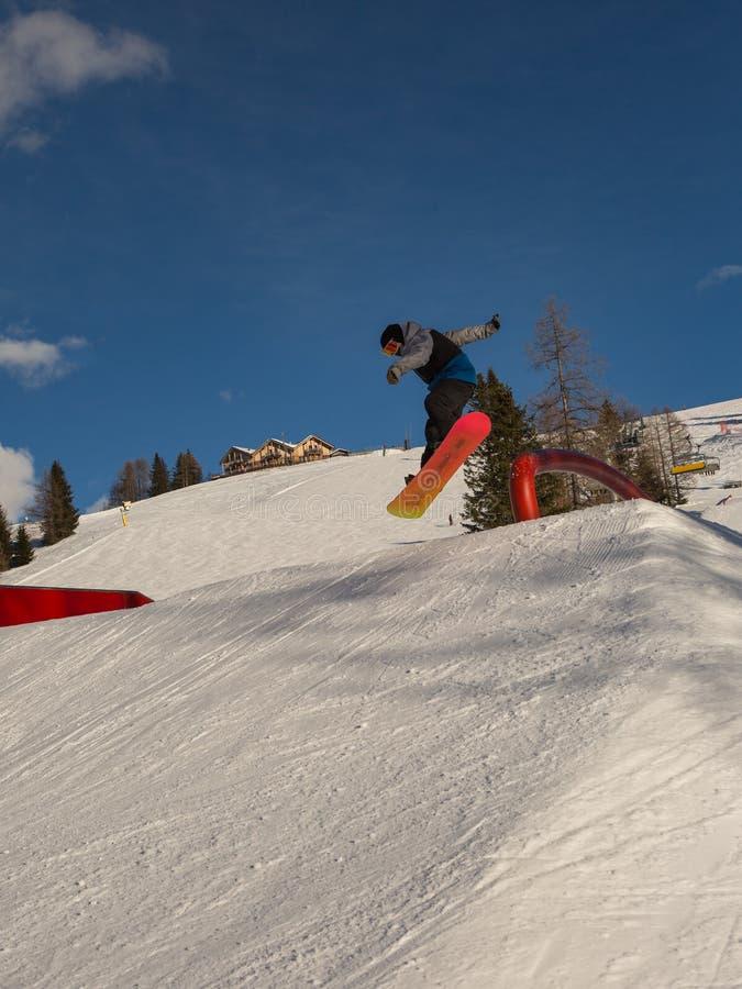Snowboarder w akci: Skakać w Halnym Snowpark obrazy stock