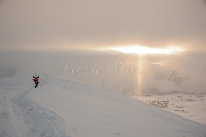 Snowboarder walking on the high mountain peak under the sun rays stock images