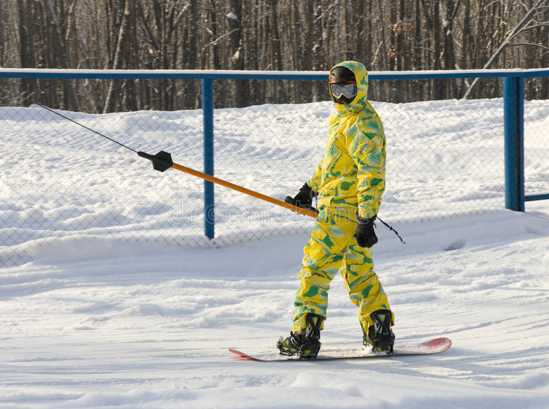 Snowboarder in a yellow suit stock photos