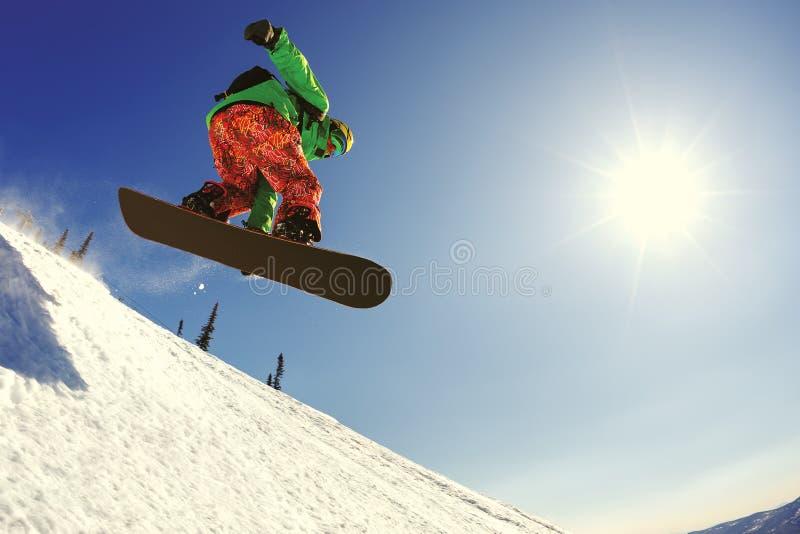 Snowboarderbanhoppning från språngbrädan mot himlen royaltyfria bilder