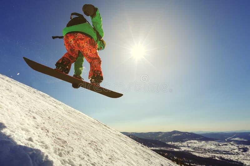 Snowboarderbanhoppning från språngbrädan mot himlen royaltyfri foto