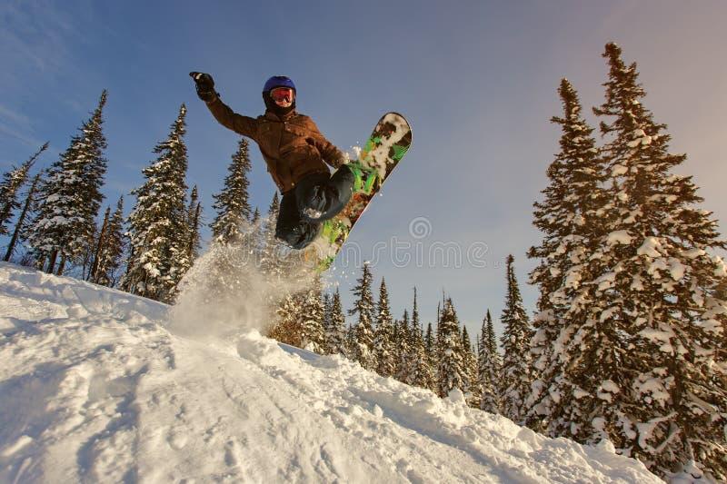 Snowboarderbanhoppning till och med luft med djupblå himmel i bakgrund arkivfoton