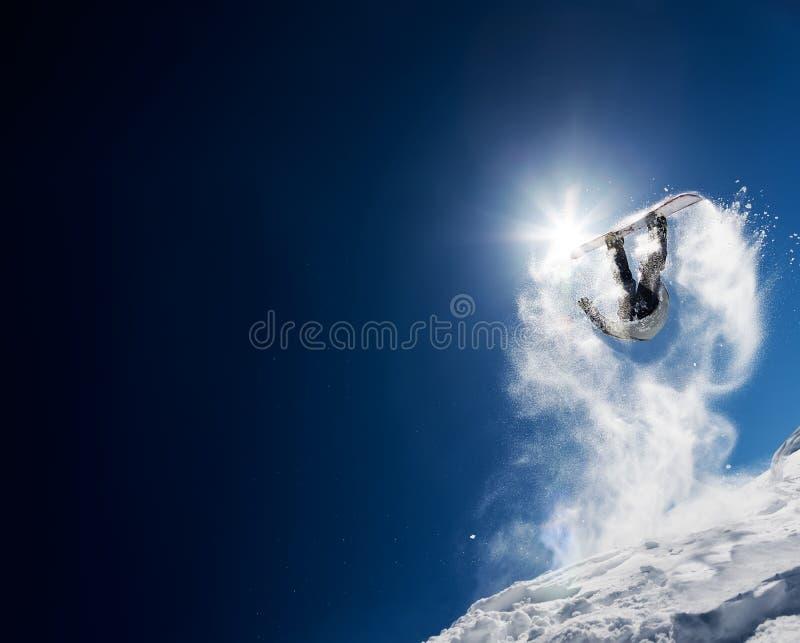 Snowboarderdanandehöjdhopp i klar blå himmel arkivfoto