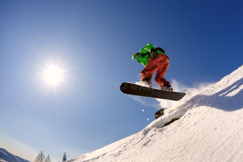 Snowboarderen hoppar från språngbrädan mot den blåa himlen arkivbild