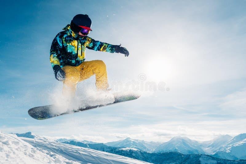 Snowboarderen hoppar i solstrålen fotografering för bildbyråer