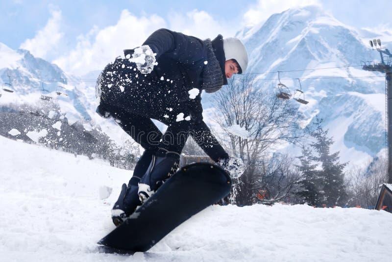 Snowboarderen hoppar med snowboarden från snowhill Landskap för manbanhoppningberg i bakgrund Snowboarderskidåkning i höjdpunkt arkivbild