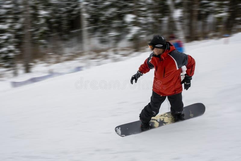 Snowboarderen i vinter parkerar går ner kullen fastar mycket royaltyfri foto