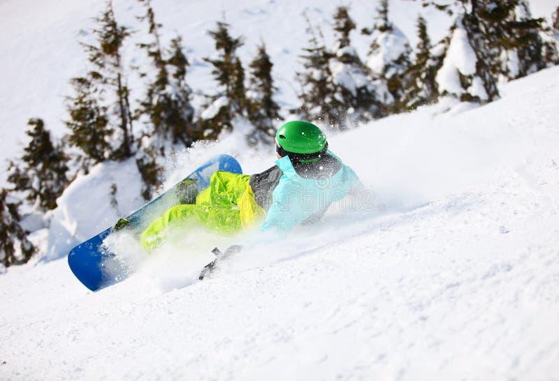 Snowboarderen, når han har fallit på ett berg, sluttar royaltyfri bild
