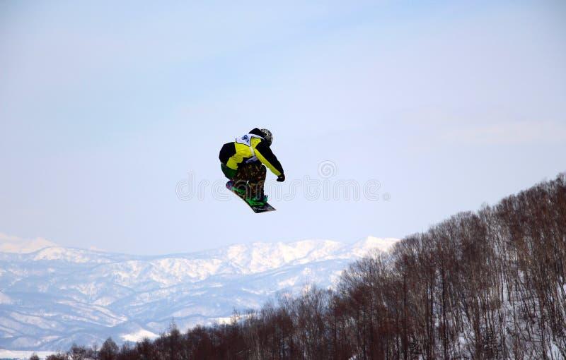Snowboarderen som av går ett stort hopp i hanazono, parkerar royaltyfri foto