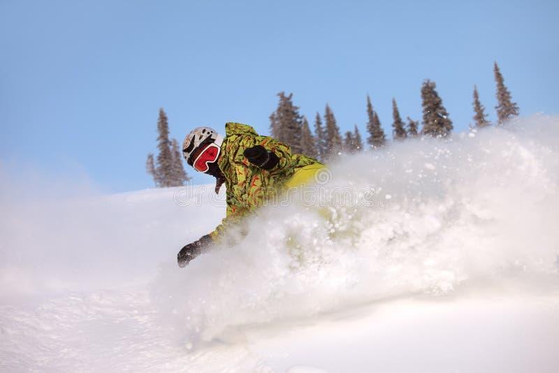 Snowboarderen som gör en tåsida, snider arkivfoto