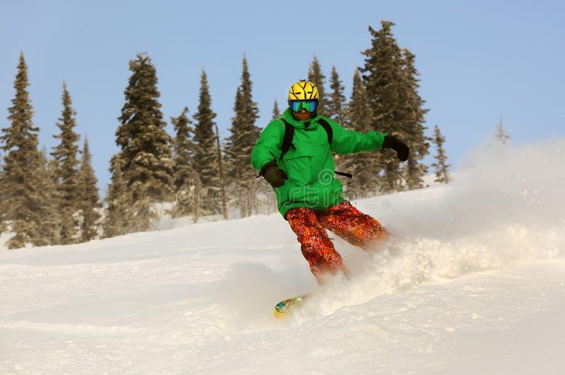 Snowboarderen som gör en tåsida, snider med djupblå himmel i backgro arkivfoton