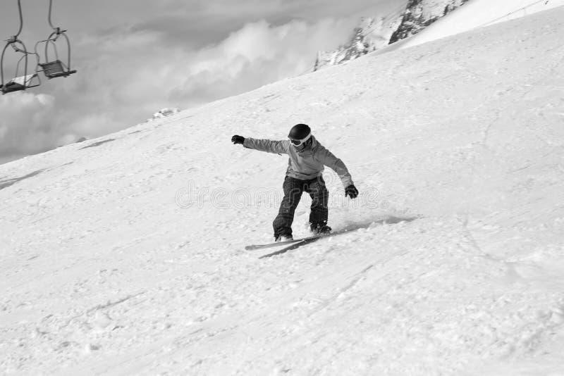 Snowboarderen som hoppar på snöig, skidar lutningen, den gamla stolelevatorn och clody himmel royaltyfri foto