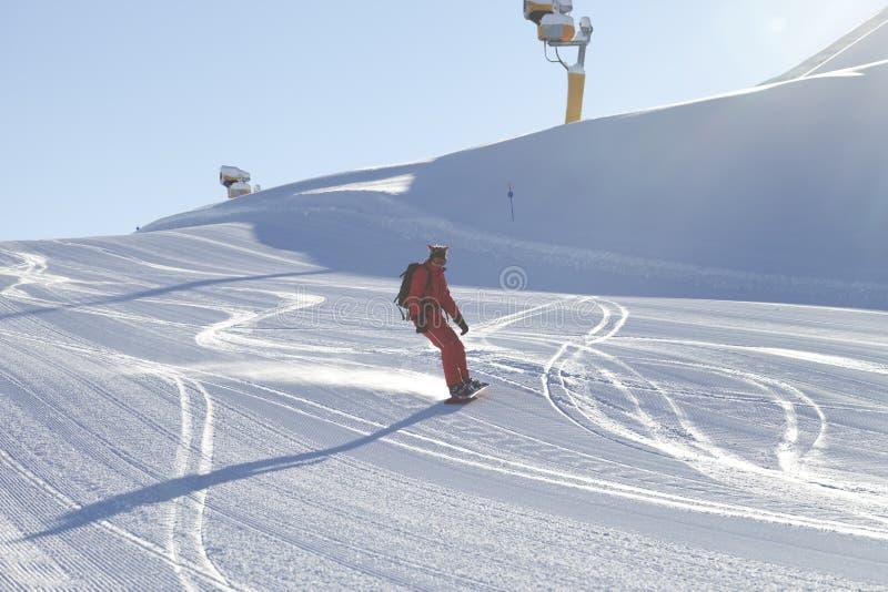 Snowboarderen stiger ned p? sn?ig skidar lutningen royaltyfri fotografi