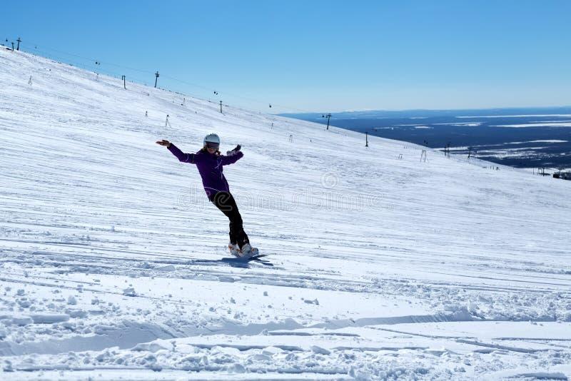 Snowboarderflickan rider och ler arkivbilder