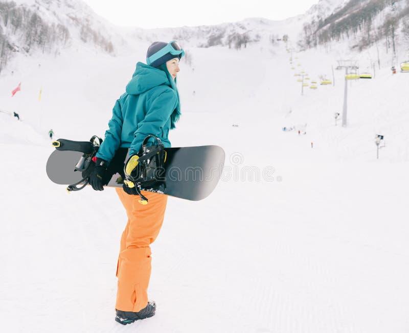 Snowboarderflickan skidar på semesterorten fotografering för bildbyråer