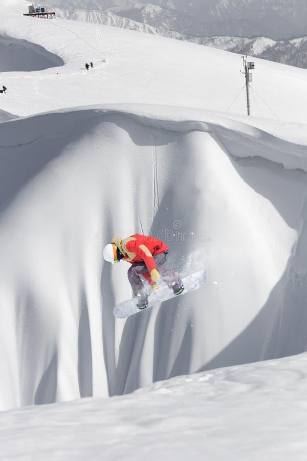 Snowboarderfliegen auf dem Hintergrund der schneebedeckten Steigung Extremer Wintersport, Snowboarding lizenzfreie stockfotos