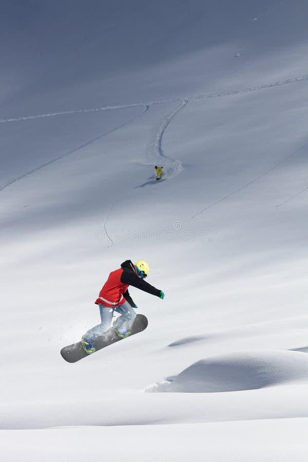 Snowboarderfliegen auf dem Hintergrund der schneebedeckten Steigung Extremer Wintersport, Snowboarding stockfoto