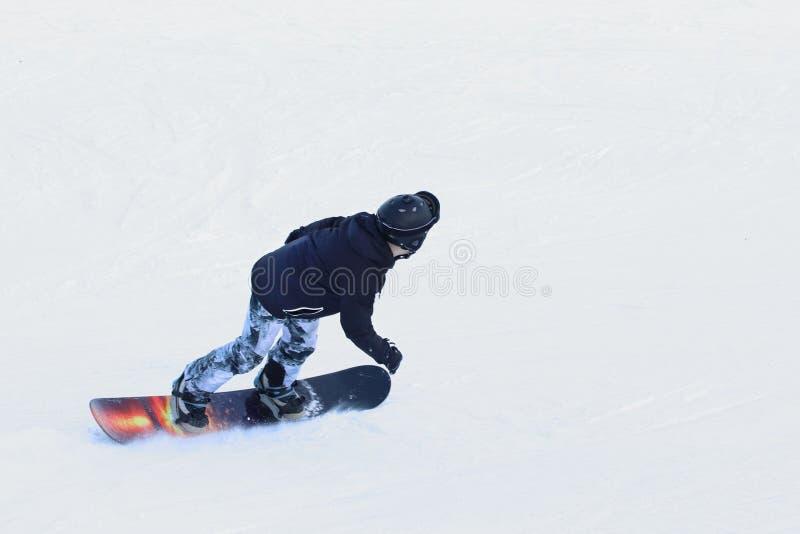 Snowboarderreiten auf einem Snowboard hinunter die schneebedeckte Steigung an einem Skiort Skispuren im Schnee Freistil- und Slal lizenzfreie stockbilder