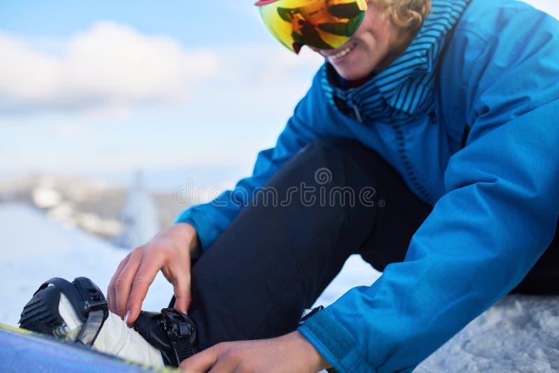 Snowboarderremmar i hans ben i snowboardkängor i moderna snabba flödesband med remmar Ryttaren på skidar semesterorten förbereder royaltyfri fotografi