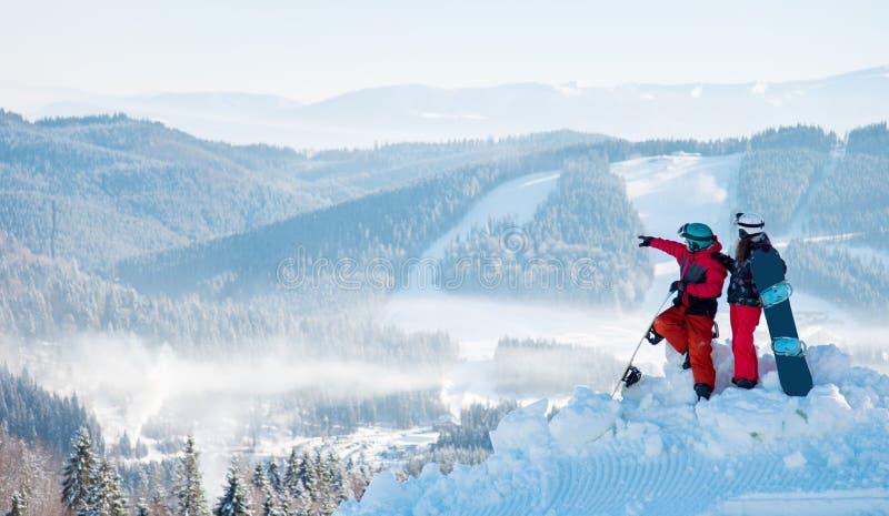 2 snowboarders наслаждаясь естественным ландшафтом, отдыхая поверх горы на солнечный зимний день на лыжном курорте стоковые фотографии rf