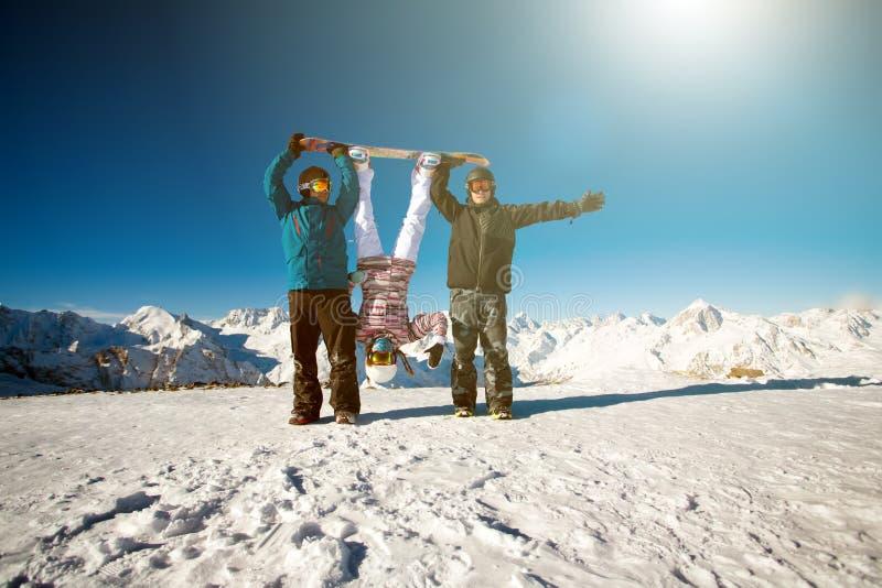 Snowboarders друзей группы имеют потеху на наклоне стоковое изображение