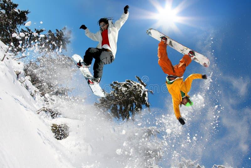 Snowboarders die tegen blauwe hemel springt stock afbeelding