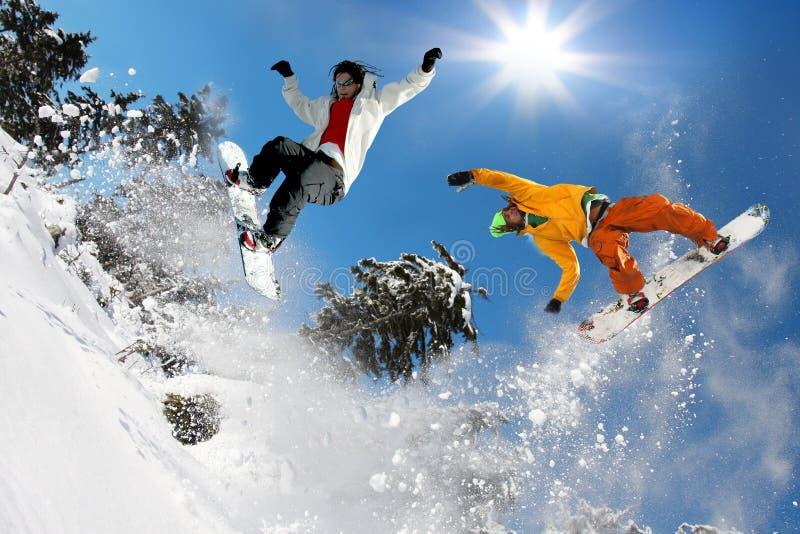 Snowboarders die tegen blauwe hemel springt stock fotografie