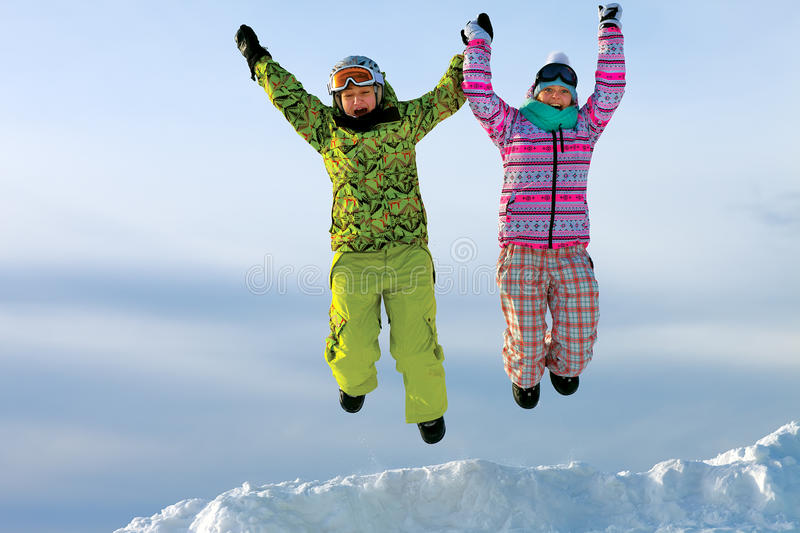 Snowboarders friends in bright vivid clothes jumping stock images
