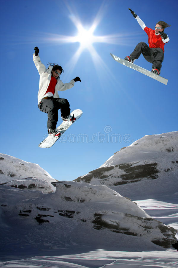 Snowboarders jumping against blue sky royalty free stock images